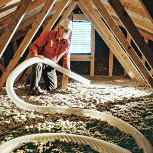 man blowing in attic insulation