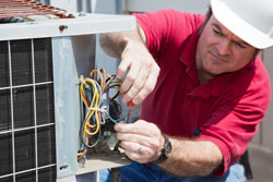 Extreme Comfort Air Conditioning & Heating Repair Technician installing new capacitor on AC Repair service call